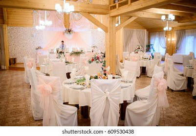 Cosy wooden restaurant hall decorated for wedding dinner