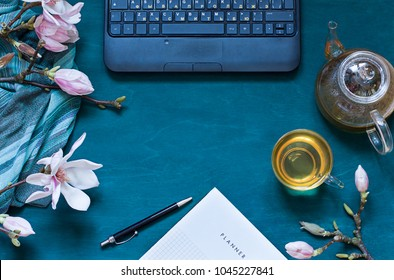 Cosy work space flat lay with magnolia flowers, laptop and green tea, Top view spring composition