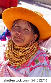 COTACACHI, ECUADOR - AUGUST 12, 2016: Woman in an orange hat and traditional dress giving a television interview at Muyu Raymi, the indigenous seed festival
