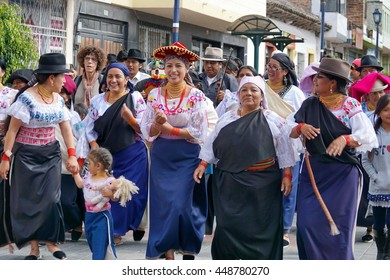COTACACHI, ECUADOR - JULY 1, 2016: Women parade on the last day of Inti Raymi, the Quechua solstice celebration.  Women and children in traditional dress march into the square to dance.