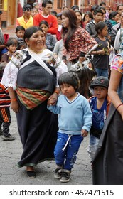 COTACACHI, ECUADOR - JULY 1, 2016: Women parade on the last day of Inti Raymi, the Quechua solstice celebration.  Woman dances with two young boys in the dance circle.