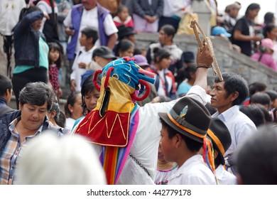 COTACACHI, ECUADOR - JUNE 23, 2016: Inti Raymi, the Quechua solstice festival, children's parade.  Man in a devil mask leads a group.