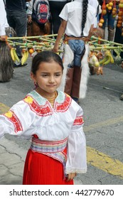 COTACACHI, ECUADOR - JUNE 23, 2016: Inti Raymi, the Quechua solstice festival, children's parade.  Young girl in a red skirt and embroidered blouse, in front of the offerings.