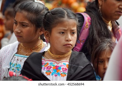 COTACACHI, ECUADOR - JUNE 23, 2016: Children parade on the first day of Inti Raymi, the Quechua solstice celebration.  A young girl marches in traditional dress.