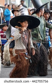 "COTACACHI, ECUADOR - JUNE 24, 2016: Inti Raymi, the Quechua solstice celebration, with a history of violence in Cotacachi.  Boy joins the men's procession to ""take the square."""