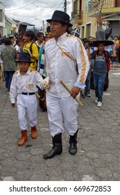COTACACHI, ECUADOR - JUNE 24, 2017: Young boy parading with his father in the men's parade in Inti Raymi, the indigenous solstice festival, with a history of violence in the village