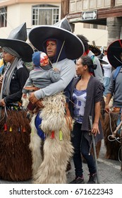 COTACACHI, ECUADOR - JUNE 25, 2017: Man parades with his young son at the men's parade at Inti Raymi, the indigenous solstice festival with a history of violence in the village
