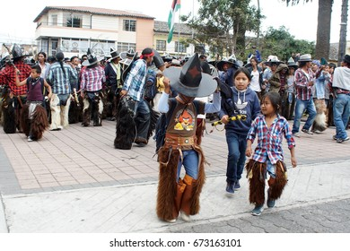 COTACACHI, ECUADOR - JUNE 25, 2017: Children march in the men's parade in Inti Raymi, the indigenous solstice festival, with a history of violence in the village