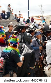 COTACACHI, ECUADOR - JUNE 29, 2016: Inti Raymi, the Quechua solstice celebration, with a history of violence in Cotacachi.  Man in a devil mask and in a Batman costume stomp and dance.