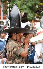 COTACACHI, ECUADOR - JUNE 29, 2016: Inti Raymi, the Quechua solstice celebration, with a history of violence in Cotacachi.  Man in a black hat blows a conch shell horn.