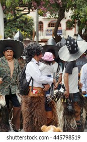 COTACACHI, ECUADOR - JUNE 29, 2016: Inti Raymi, the Quechua solstice celebration, with a history of violence in Cotacachi.  Man dances with his infant daughter in his arms.