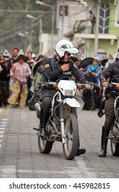 COTACACHI, ECUADOR - JUNE 29, 2016: Inti Raymi, the Quechua solstice celebration, with a history of violence in Cotacachi.  Police on motorcycles lead a group into the square from an outlying village.