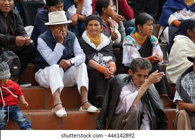 COTACACHI, ECUADOR - JUNE 30, 2016: Inti Raymi, the Quechua solstice celebration, with a history of violence in Cotacachi.  Spectators sit on the church steps to watch the procession.
