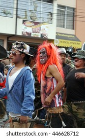 COTACACHI, ECUADOR - JUNE 30, 2016: Inti Raymi, the Quechua solstice festival, with a history of violence in town.  Man in a red wig and devil costume dances to awaken Mother Earth.