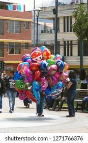 COTACACHI, ECUADOR - NOVEMBER 1, 2018: Helium balloon vendor in Matriz Park on the Day of the Dead