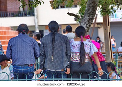 COTACACHI, ECUADOR - NOVEMBER 1, 2019: Young people on a fence in Matriz Park for Day of the Dead