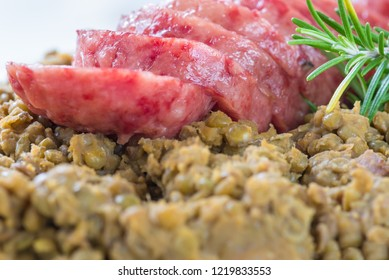 Cotechino (pork sausage) with lentils. Traditional Italian dish.  According to tradition, it is served with lentils on New Year's Eve, because it is said that lentils bring money for the coming year