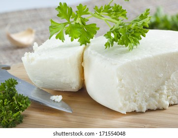 Cotija cheese with cilantro on cutting board .