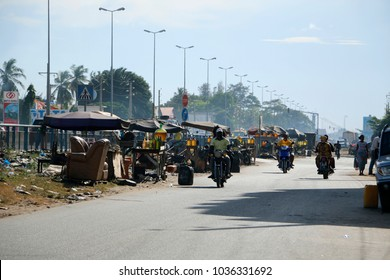 Cotonou Benin April 30 2014 Street with lots of petrol sellers Many taxi motorbikes on the street