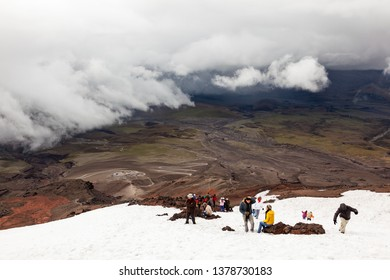 Cotopaxi, Ecuador, May 22, 2108: A group of tourists enjoy the snow in the Cotopaxi volcano, in a day of climatic contrasts, with rain clouds in the lower part and a little light above