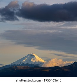 Cotopaxi volcano at sunset with overflying airplane, Quito, Cotopaxi province, Ecuador.