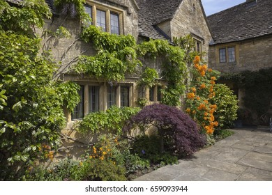 Cotswold cottage with pretty flower border, England