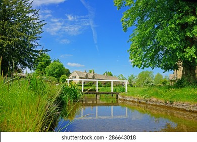 Cotswold cottages and bridge over the River Eye on a summers day in the popular tourist destination of Lower Slaughter, (Its Doomsday book entry was Sclostre) The Cotswolds, Gloucestershire, U K