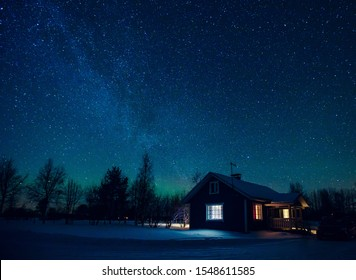 Cottage against the night sky with the Milky Way and the arctic Northern lights Aurora Borealis in snow winter Finland, Lapland
