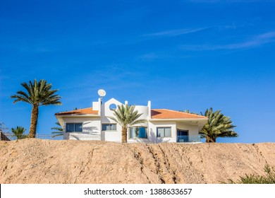 cottage apartment building of edge of cliff sand stone rock in south desert environment in Israel with palm trees in garden and vivid blue sky background, copy space