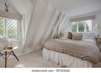 Cottage bedroom decorated in a light modern style with neutral color including bed with quilt and cushions, leaded windows and numerous roof timbers