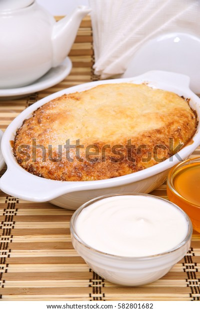 Cottage cheese - apple casserole on a white plate with sour cream and jam with filing for tea