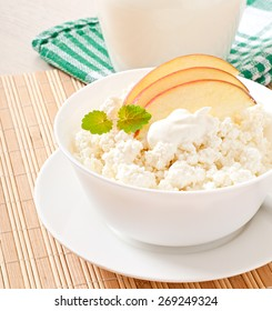 Cottage cheese with apples and sour cream for breakfast close up