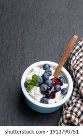 Cottage  cheese with blueberry jam in ceramic bowl on black stone background