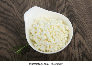 Cottage cheese in the bowl over wooden