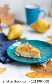 Cottage cheese casserole with pears on a blue plate on a white background with autumn leaves