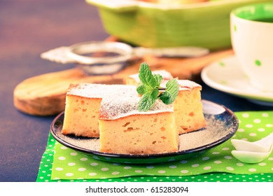 Cottage cheese casserole and tea against a dark background. Selective focus. The image is tinted
