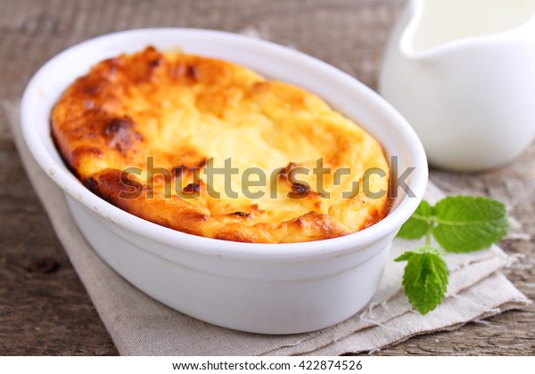 Cottage cheese casserole in white dish decorated with mint, on a old wooden background