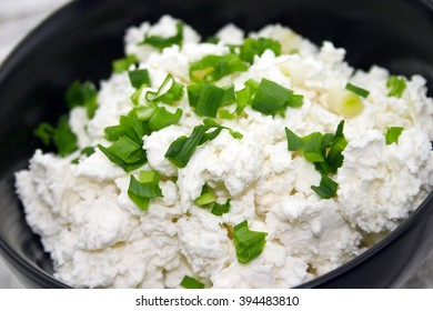 Cottage cheese with chives in black ceramic bowl on rustic wooden background. Healthy breakfast. Healthy food concept. Soft view.