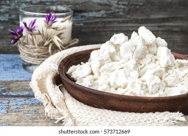 Cottage cheese in a clay plate, glass with milk on a wooden background.