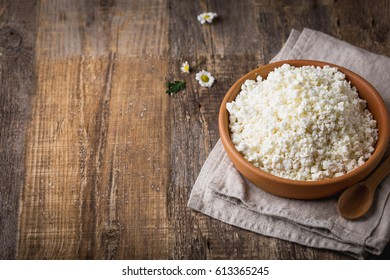 Cottage cheese in a clay pot with a wooden spoon closeup on wooden background. Clay pots with fresh milk. Copy space. A rustic style.