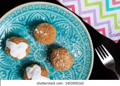 Cottage cheese dumplings with breadcrumbs and powdered sugar on a rustic plate