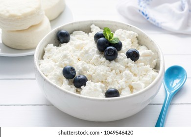 Cottage cheese, farmers cheese or tvorog in white bowl on white wooden table, closeup view