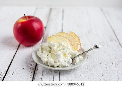 Cottage cheese, honey and Apple on a plate on white wooden background. Selective focus. Healthy eating.