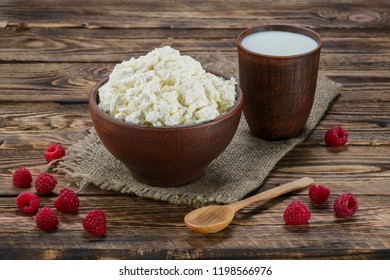 Cottage cheese and milk in clayware on wooden table, sackcloth table-napkin and wooden spoon