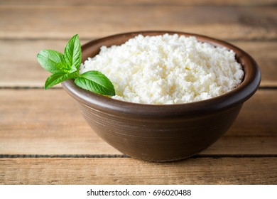 Cottage cheese and mint in ceramic bowl on rustic wooden table. Selective focus.