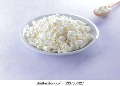 Cottage cheese on white plate with wooden spoon. Cottage cheese on white background. Soft cheese for diet. Healthy dairy product for breakfast