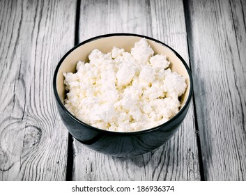 Cottage cheese on wooden board .