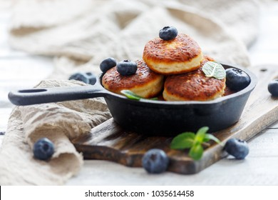 Cottage cheese pancakes and blueberries in a pan on a white wooden table, selective focus.