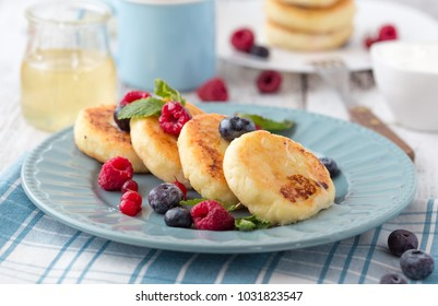 Cottage cheese pancakes. homemade  traditional Ukrainian dish ( syrniki ) with honey and sour cream.