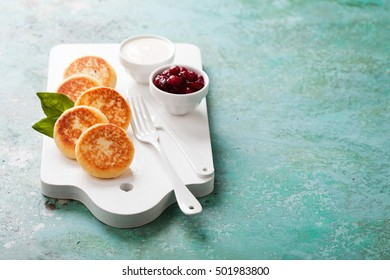 Cottage cheese pancakes Russian syrniki with cranberry jam and yogurt, selective focus